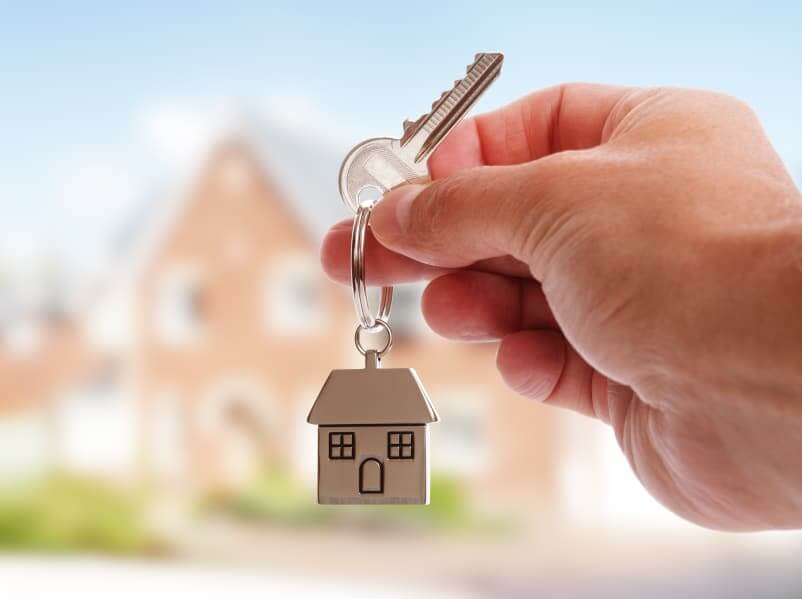 A Hand Holding House Keys On House Shaped Keychain In Front Of A New Home