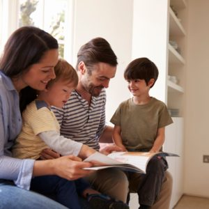 family-sitting-on-window-seat-reading-story-at-PRSTHQ8-web